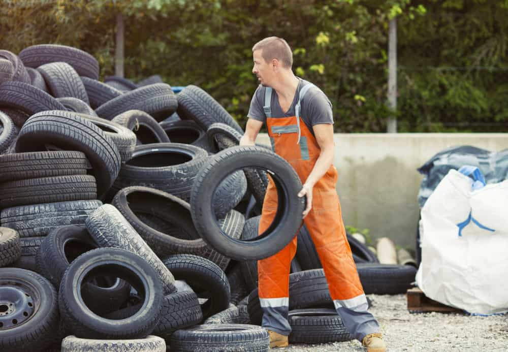 Man in orange workwear sorting recycled tyres