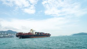 Container vessel sailing away with financed goods for global trade