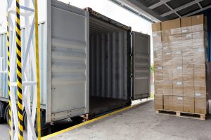 Loading shipping container for export with packing declaration document.