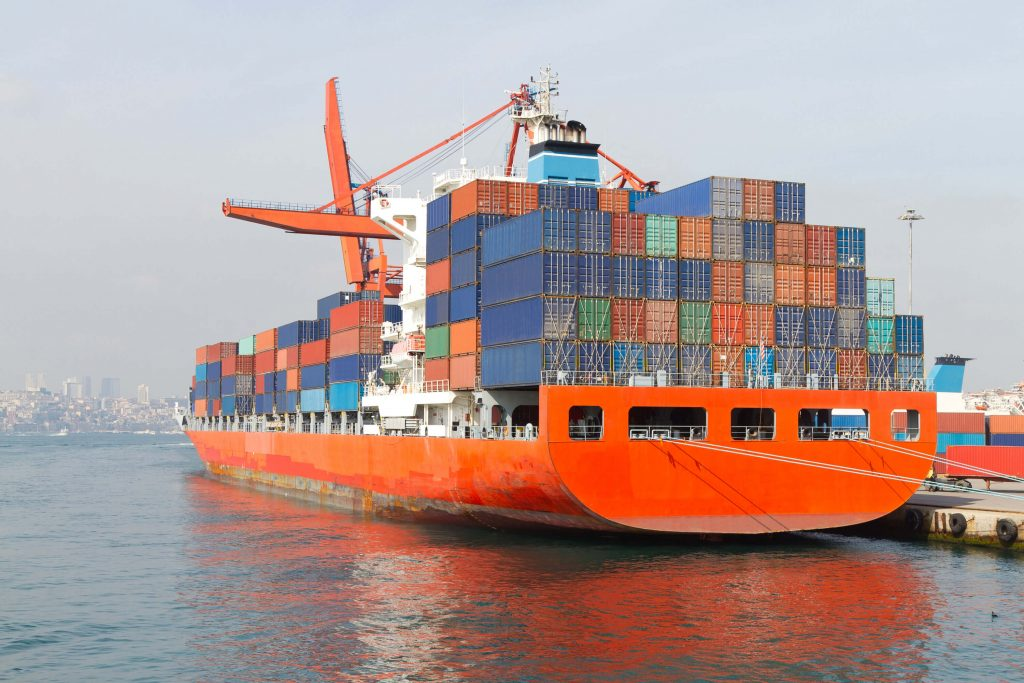 Shipping vessel with containers docked at a port